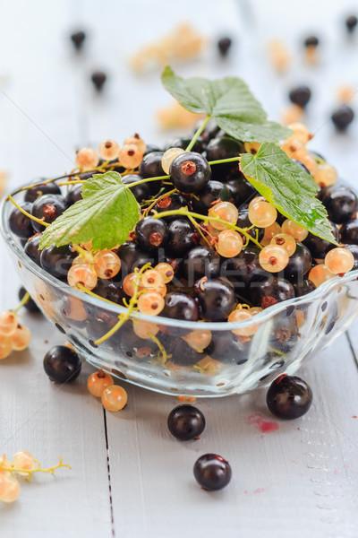 Gyümölcsök fehér fekete csészealj fa asztal gyümölcs Stock fotó © fotoaloja