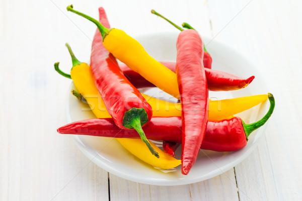 Piros citromsárga chilipaprika felszolgált tányér tűz Stock fotó © fotoaloja