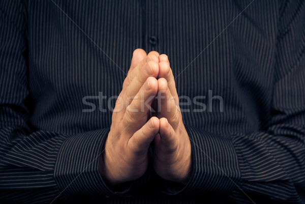Primo piano pregando uomo bianco buio shirt mano Foto d'archivio © fotoaloja