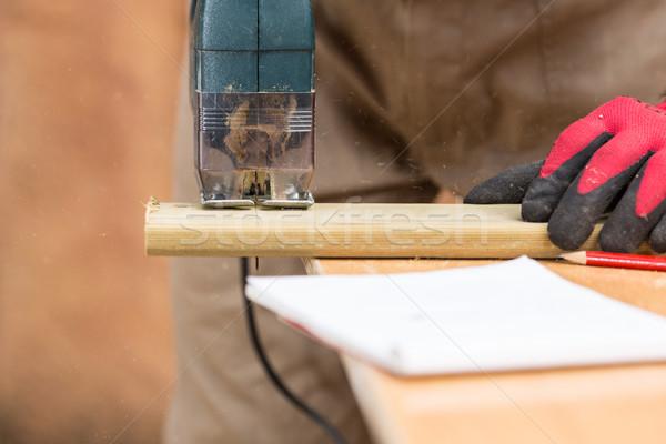 Carpenter sawing a board Stock photo © fotoedu
