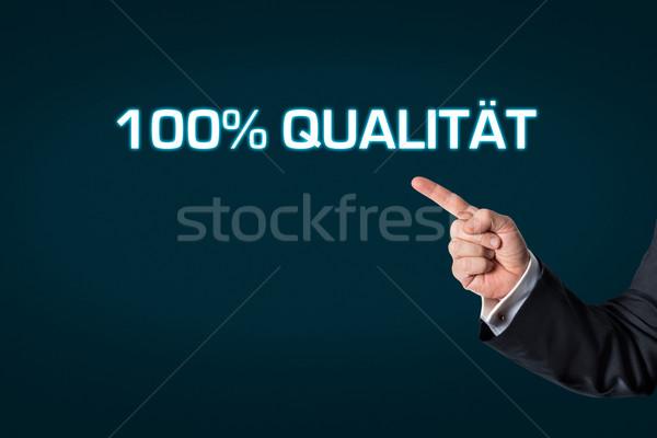 Homme d'affaires pointant mots 100 qualité sombre Photo stock © fotoquique