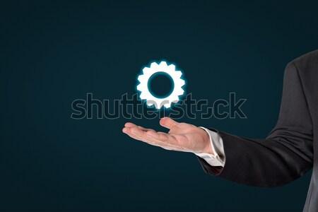 Businessman holding a virtual gear wheel symbol Stock photo © fotoquique