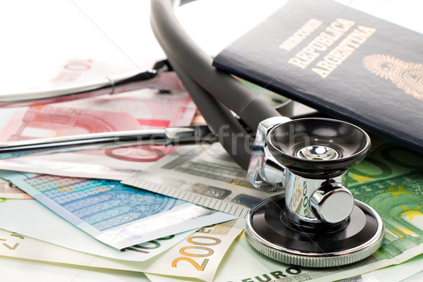 Bills with stethoscope and passport Stock photo © fotoquique