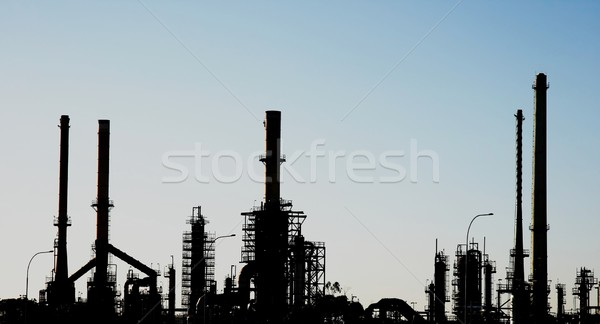 Stock photo: Silhouette of an oil refinery with chimneys