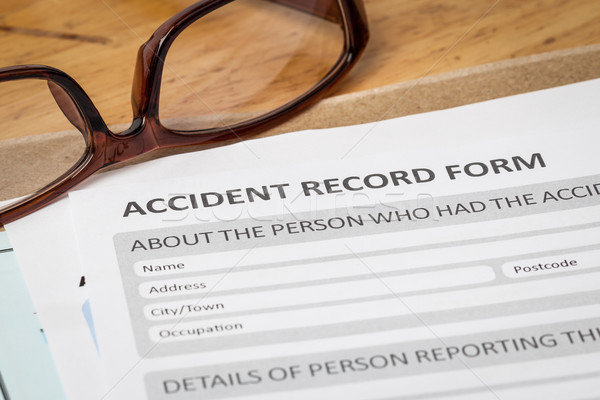 Accident report application form on brown envelope and eyeglass, Stock photo © FrameAngel