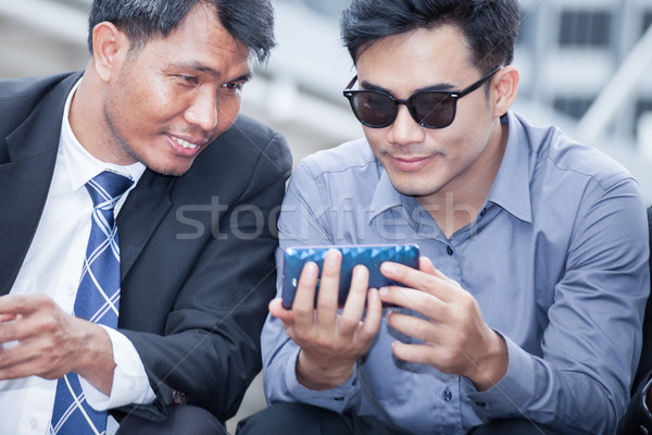 Asian businessman sitting and looking at smartphone that his col Stock photo © FrameAngel
