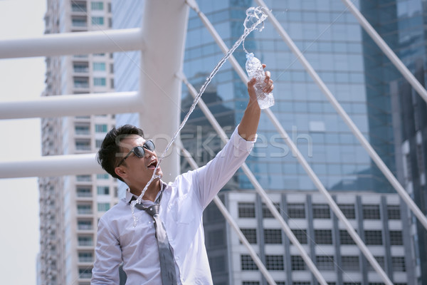 Asian Businessman standing and happy to drink water and hold bot Stock photo © FrameAngel