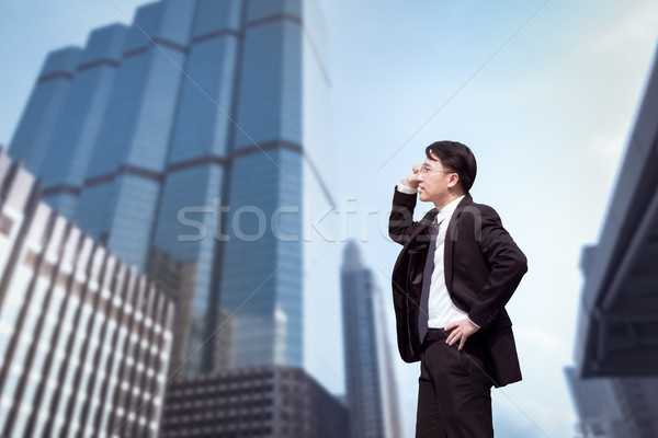 Confident Asian Businessman standing and looking at city for vis Stock photo © FrameAngel