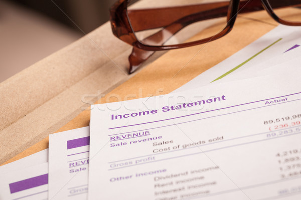 Income statement letter on brown envelope and eyeglass, business Stock photo © FrameAngel