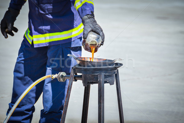 fire trainer teach pouring oil into pan flames for conflagration Stock photo © FrameAngel