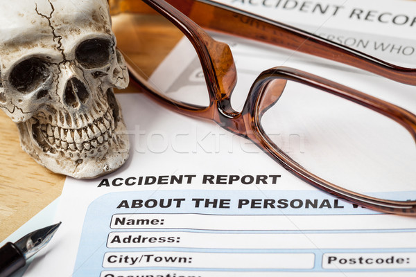 Accident report application form and human skull on brown envelo Stock photo © FrameAngel