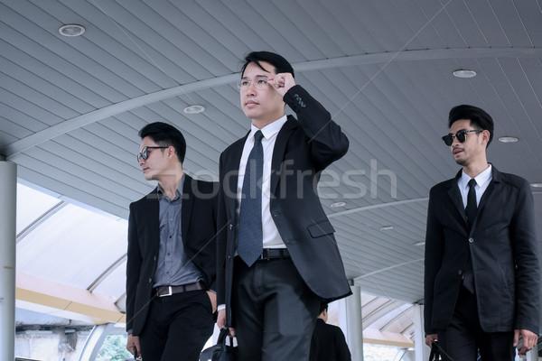 Asya iş adamı grup koruma yürüyüş iş Stok fotoğraf © FrameAngel