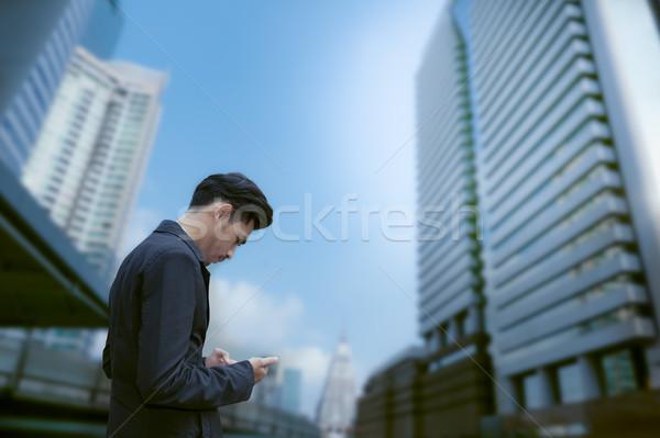 Asian zakenman permanente smartphone business gebouw Stockfoto © FrameAngel