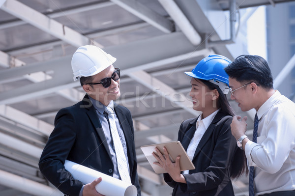 Asian businessman and woman discuss with engineer architect prof Stock photo © FrameAngel