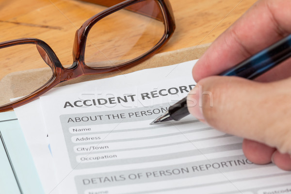 Accident report application form and human hand with pen on brow Stock photo © FrameAngel