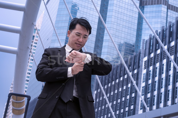 Asian Confident business man watching time for appointment and m Stock photo © FrameAngel