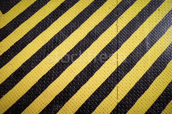 yellow and black marking warning sign, grunge background Stock photo © FrameAngel