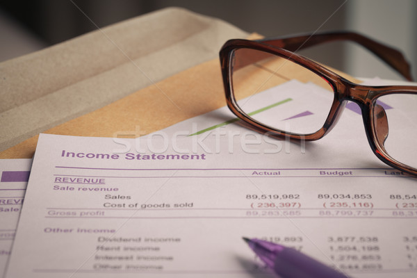 Income statement letter on brown envelope and eyeglass, pen,  bu Stock photo © FrameAngel