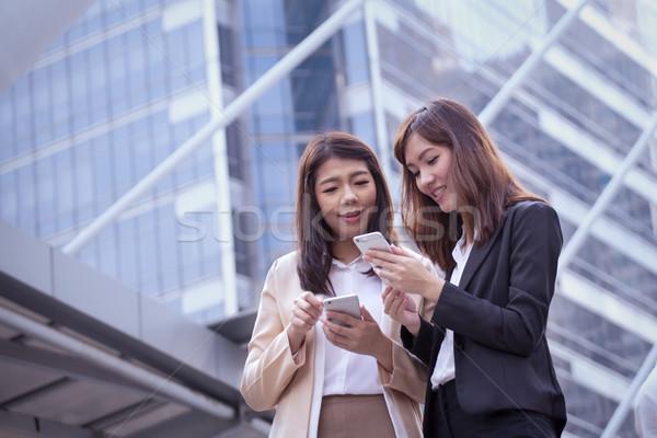 アジア ビジネス女性 携帯電話 同僚 議論 トピック ストックフォト © FrameAngel