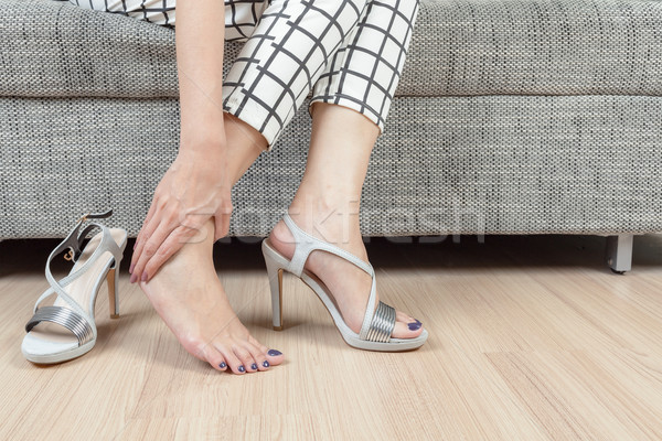 woman sit on chair and female hand with foot pain after, take sh Stock photo © FrameAngel