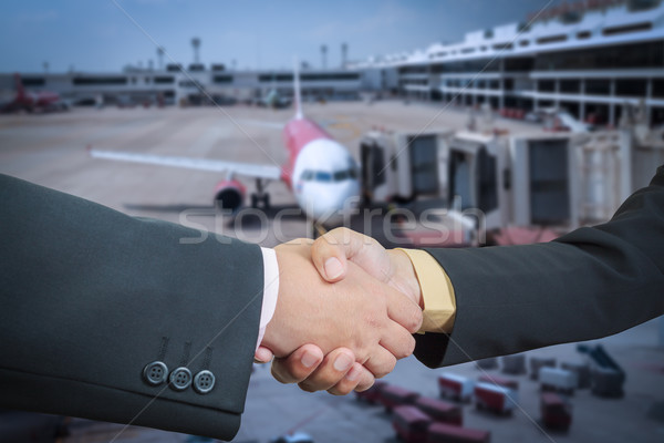 Businessman handshake with air plane transportation logistic bac Stock photo © FrameAngel
