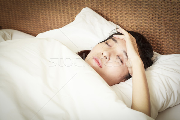 woman with headache lying on bed Stock photo © FrameAngel