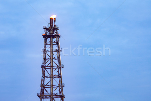 Tower chimney of Oil refinery with fire on top on blue cloud sky Stock photo © FrameAngel