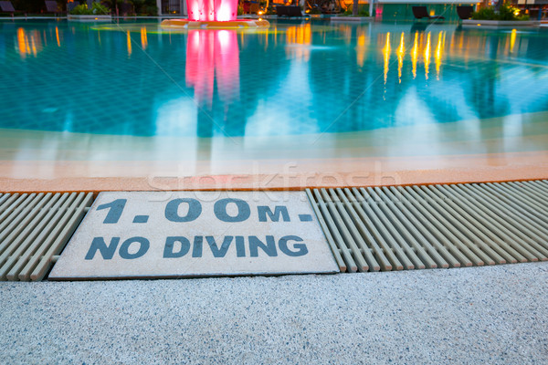 warning sign '1.00m No Diving' at Swimming pool of luxury hotel Stock photo © FrameAngel