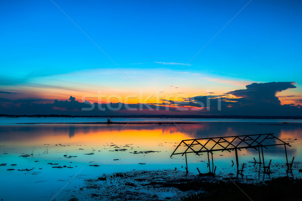 sunset sky over lake or river and home with flood at twilight Stock photo © FrameAngel