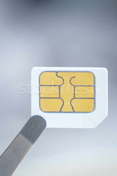 Sim card for smart mobile phone with tweezer, close up Stock photo © FrameAngel
