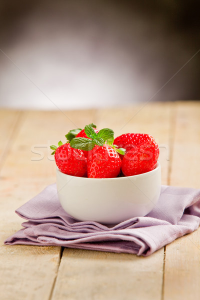 Strawberries on wooden table with violet napkin Stock photo © Francesco83