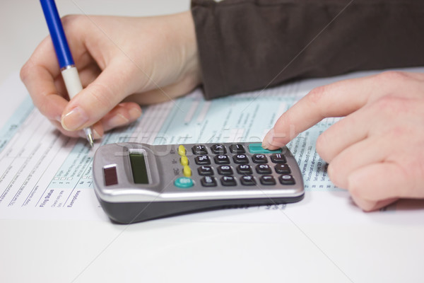 Filling income tax forms with calculator and pen Stock photo © frank11