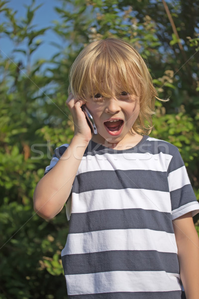 Atractive surpriced blond boy is calling Stock photo © frank11