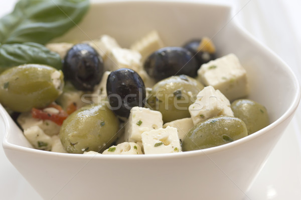 Salad of olives, served with chunks of cheese in a white bowl. Stock photo © frank11