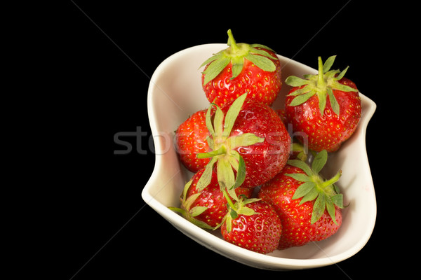 Fresh strawberries in white bowl on a black background. Stock photo © frank11