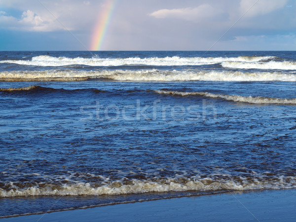 Ocean Waves Breaking on Shore with a Partial Rainbow in the Background Stock photo © Frankljr