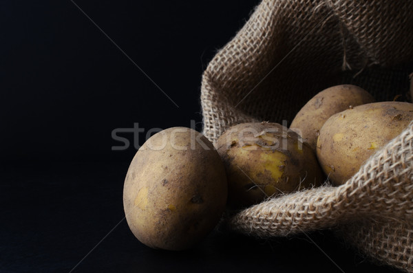 Potatoes Tipping from Hessian Sack on Black Stock photo © frannyanne