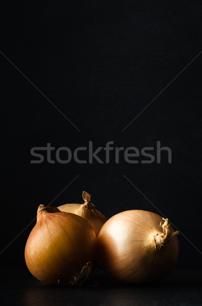 Three Whole Onions on Slate with Black Chalkboard Background Stock photo © frannyanne