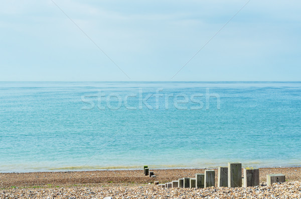 Pebble Beach on Bright Day with Wooden Posts Leading to Sea  Stock photo © frannyanne