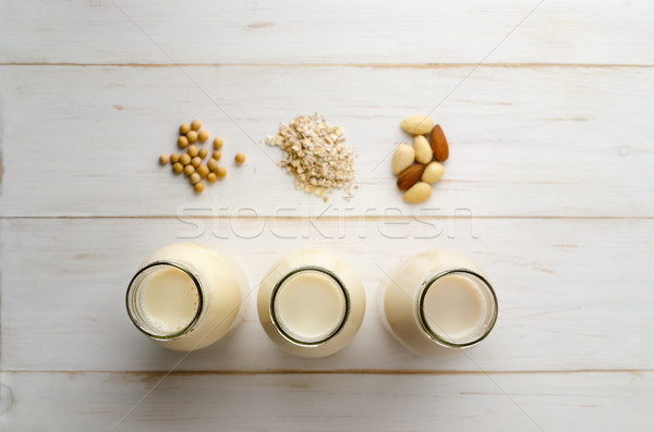 Row of Bottled Milk Substitutes with Ingredients on White Wood P Stock photo © frannyanne