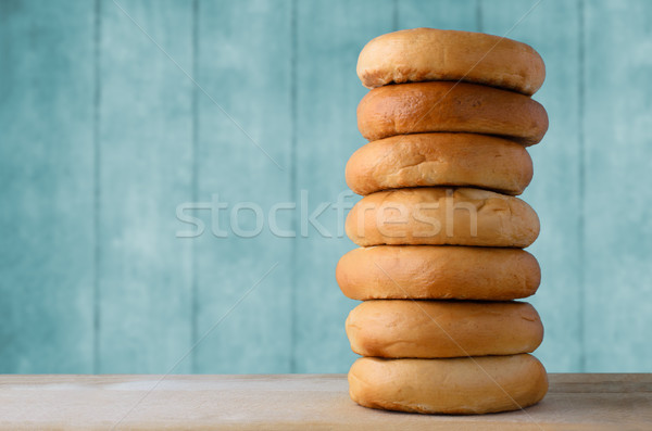 High Bagel Stack on Wood with Turquoise Blue Background Stock photo © frannyanne