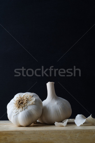 Two Garlic Bulbs on Wooden Chopping Board Stock photo © frannyanne