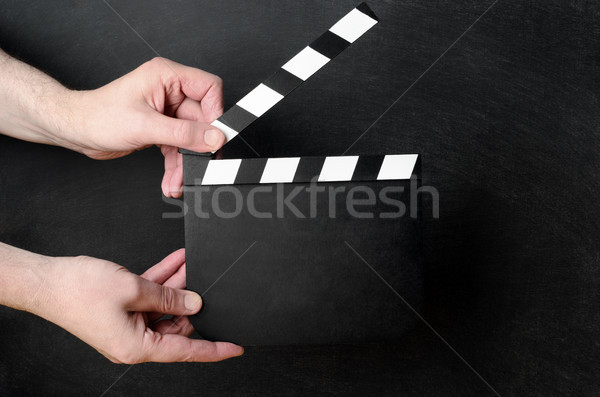 Clapperboard Held Open on Black Chalkboard Background Stock photo © frannyanne