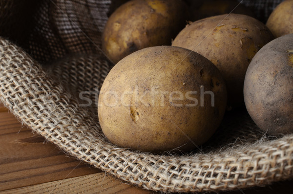 Raw Potatoes in Opened Sack on Wood Table Stock photo © frannyanne