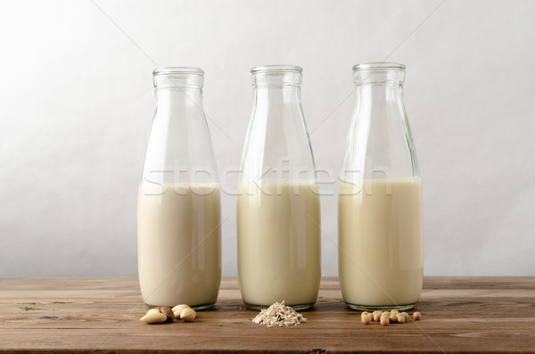 Row of Dairy Free Milk Alternatives with Ingredients on Wood Pla Stock photo © frannyanne