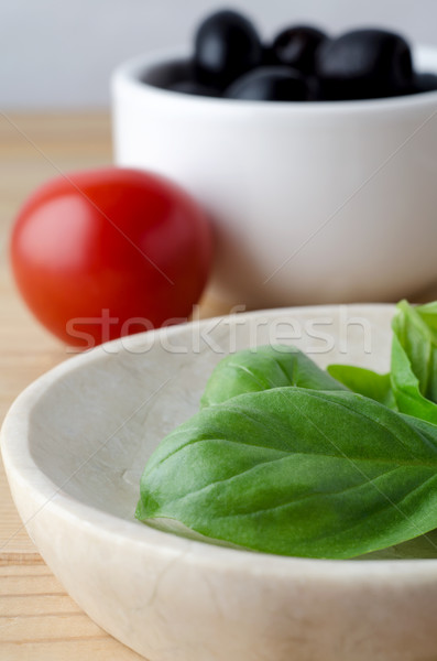 Basil Leaves, Tomato and Olives in Serving Bowls on Wood Planked Stock photo © frannyanne