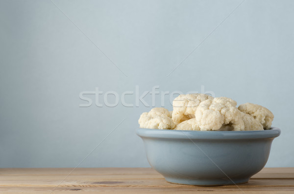 Raw Cauliflower in Bowl on Wood Plank Table with Blue Background Stock photo © frannyanne