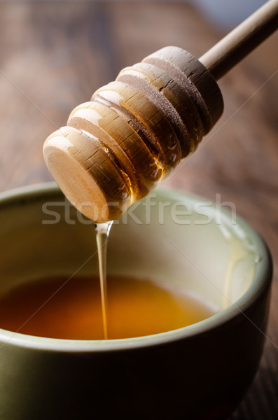 Honey Drizzler Flowing into Green Bowl on Woodem Table Stock photo © frannyanne