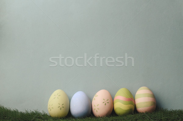 Row of Painted Easter Eggs on Grass on Blue Background Stock photo © frannyanne