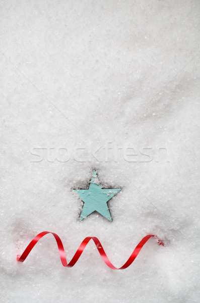 Turquoise Blue Star and Red Swirling Ribbon on Snow Stock photo © frannyanne